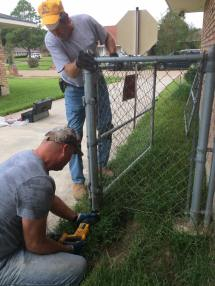 SBCV disaster relief workers remove a chain-link fence from a Baton Rouge home so that FEMA could deliver a mobile home for the resident.