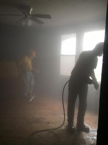 SBCV disaster relief workers power-wash the inside of a flood-damaged home.